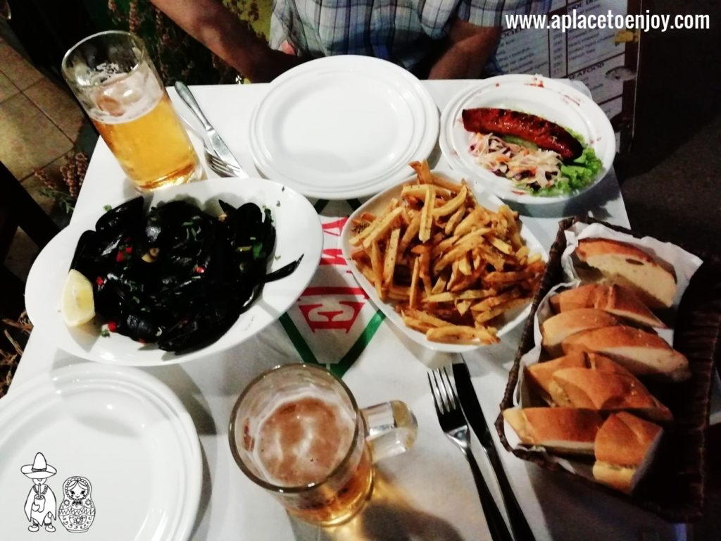 Shelled mussels, a grilled sausage with french fries and beer
